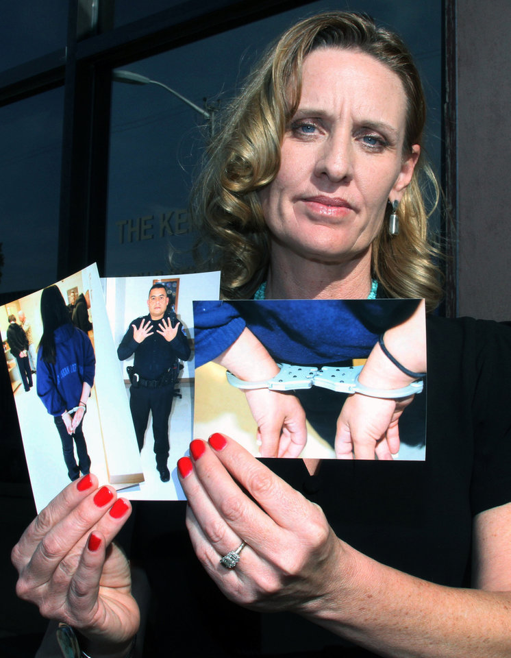 Photo -   FILE - This Jan. 26, 2012 file photo shows attorney Shannon Kennedy holding photographs of a school-aged client handcuffed for
