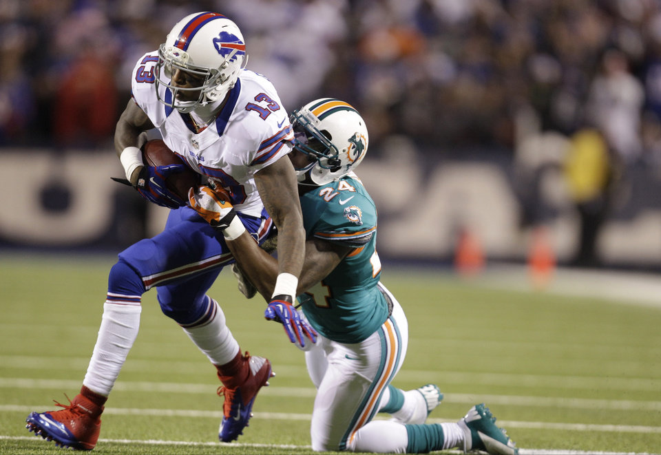 Photo -   Buffalo Bills wide receiver Steve Johnson (13) is tackled by Miami Dolphins cornerback Sean Smith (24) during the first half of an NFL football game on Thursday, Nov. 15, 2012, in Orchard Park, N.Y. (AP Photo/Gary Wiepert)
