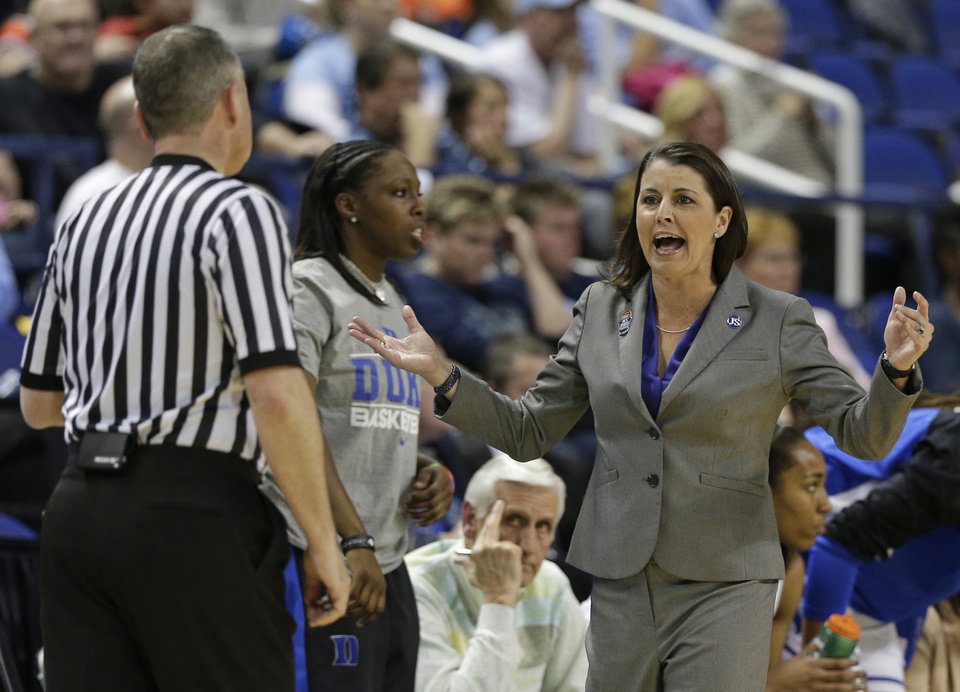 Photo - Duke head coach Joanne P McCallie, right, argues a call during the first half of an NCAA college basketball semi-final game against North Carolina at the Atlantic Coast Conference tournament in Greensboro, N.C., Saturday, March 8, 2014. (AP Photo/Chuck Burton)