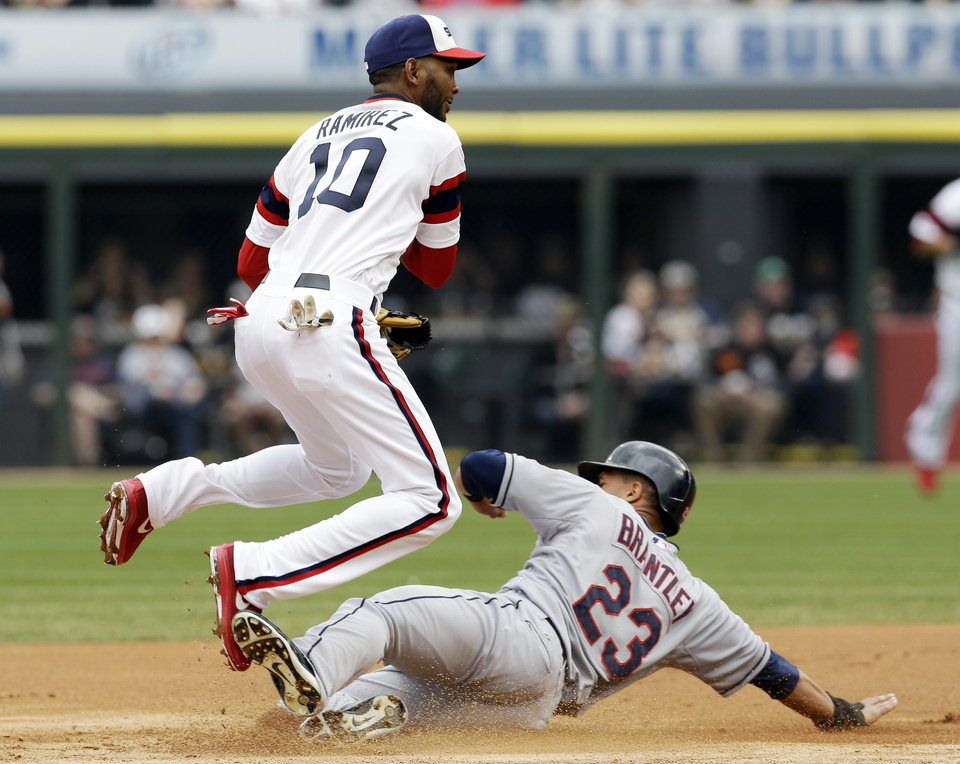 Photo - Chicago White Sox shortstop Alexei Ramirez, left, jumps after forcing out Cleveland Indians' Michael Brantley during the first inning of a baseball game in Chicago on Saturday, April 12, 2014. Asdrubal Cabrera was safe at first. (AP Photo/Nam Y. Huh)