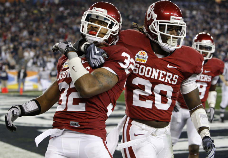 Oklahoma's Jamell Fleming (32) and Oklahoma's Quinton Carter (20) celebrate after a interception for a touchdown by Fleming during the Fiesta Bowl college football game between the University of Oklahoma Sooners and the University of Connecticut Huskies in Glendale, Ariz., at the University of Phoenix Stadium on Saturday, Jan. 1, 2011.  Photo by Bryan Terry, The Oklahoman