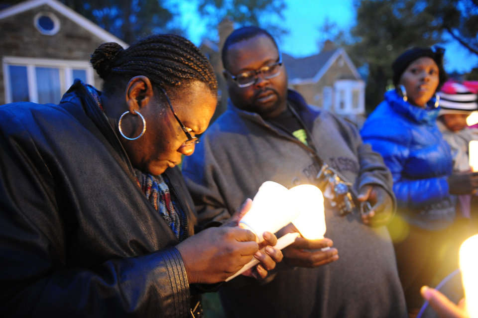 Photo - File - In this Nov. 6, 2013 file photo Charles Hannah lights Theresa Walker's candle, left,  at a vigil for Renisha McBride in the front of the home where she was shot in Dearborn Heights, Mich. Prosecutors plan to announce Friday, Nov. 15, 2013 whether they'll  charge a suburban Detroit homeowner in the shooting death of McBride. Autopsy results released after the shooting ruled McBride died of a gunshot wound to her face. (AP Photo/Detroit News, Ricardo Thomas, File)  DETROIT FREE PRESS OUT; HUFFINGTON POST OUT
