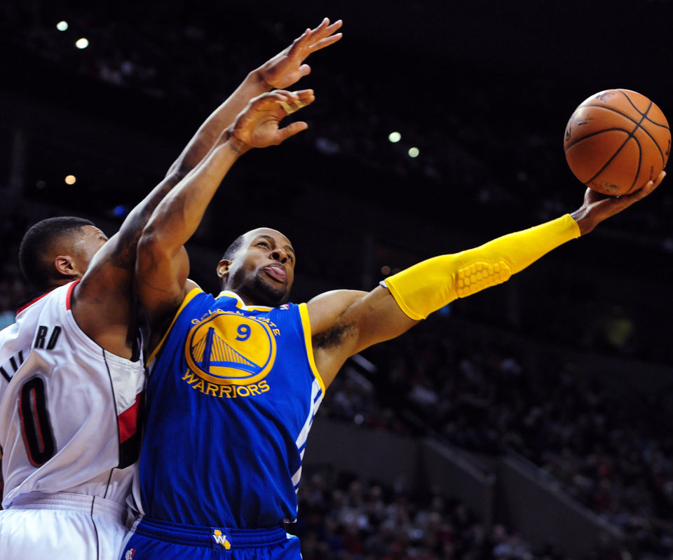 Photo - Golden State Warriors forward Andre Iguodala (9) drives to the basket on Portland Trail Blazers guard Damian Lillard (0) during the first half of an NBA basketball game in Portland, Ore., Sunday, April 13, 2014. (AP Photo/Steve Dykes)