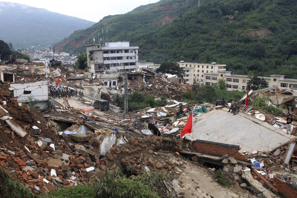 Photo - Rescue workers search for survivors among the remains of collapsed buildings in the epicenter of an earthquake that struck the town of Longtoushan in Ludian county in southwest China's Yunnan province Monday, Aug. 4, 2014. Rescuers dug through shattered homes Monday looking for survivors of the strong earthquake that toppled thousands of homes on Sunday, killing hundreds and injuring more than a thousand people. (AP Photo) CHINA OUT