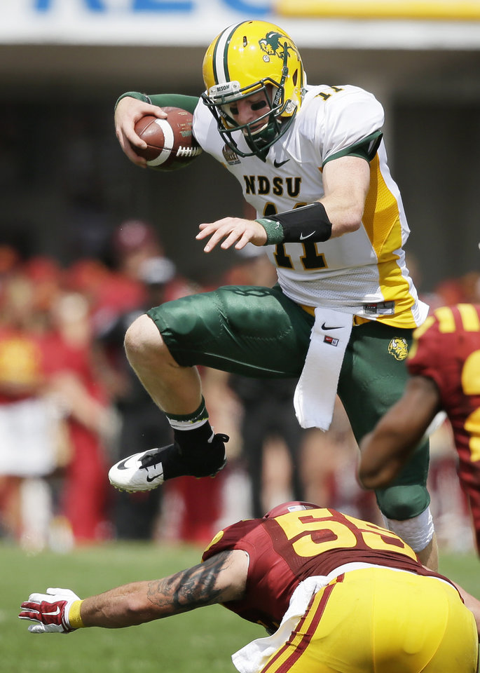 Photo - North Dakota State quarterback Carson Wentz (11) leaps over Iowa State linebacker Jevohn Miller during the second half of an NCAA college football game, Saturday, Aug. 30, 2014, in Ames, Iowa. North Dakota State won 34-14. (AP Photo/Charlie Neibergall)