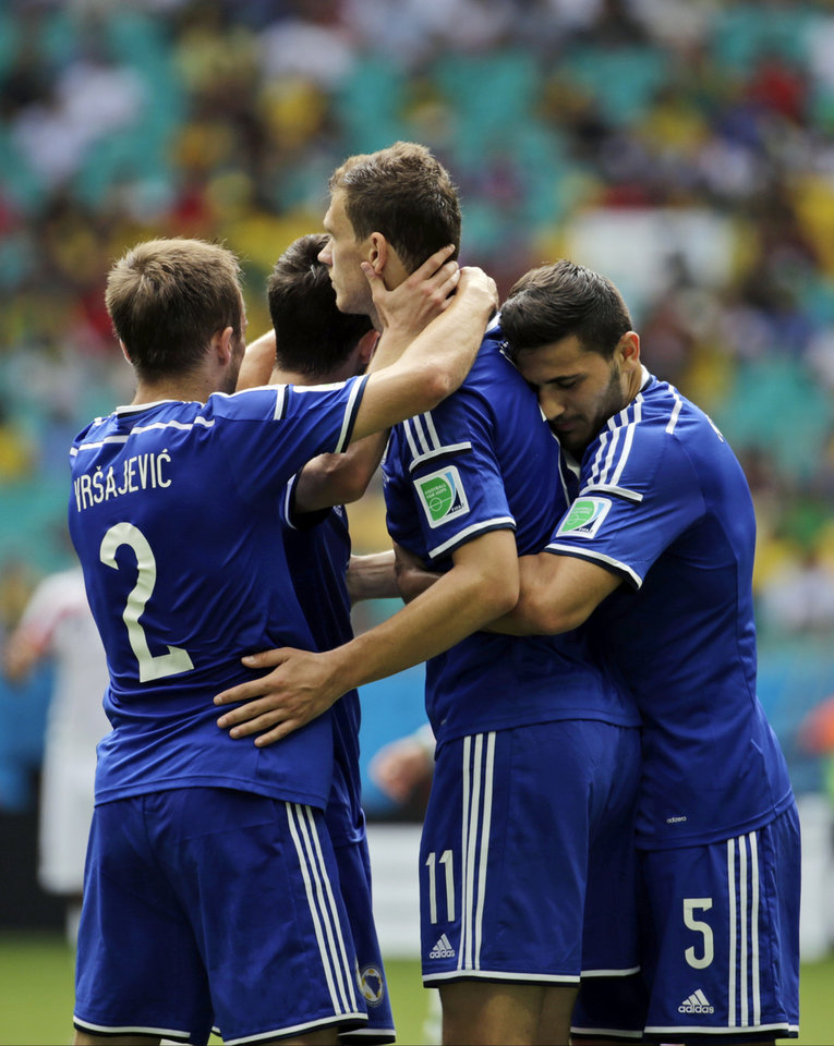 Photo - Bosnia's Edin Dzeko, center, is greeted by his teammates after scoring the opening goal during a group F World Cup soccer match between Bosnia and Iran at the Arena Fonte Nova in Salvador, Brazil, Wednesday, June 25, 2014. (AP Photo/Fernando Llano)