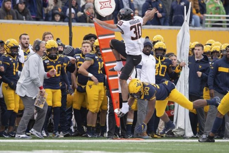 Photo -  Oklahoma State running back Chuba Hubbard flies out of bounds after hurdling a West Virginia defender Saturday. [Bruce Waterfield/OSU Athletics]