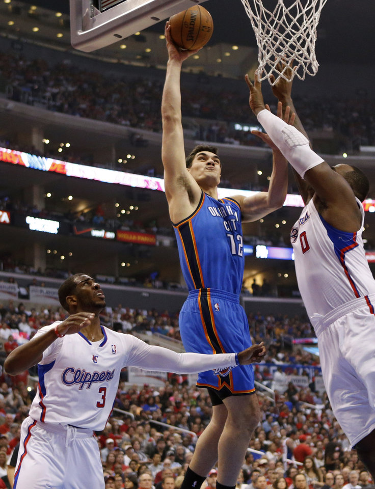 Photo - Oklahoma City's Steven Adams (12) goes to the basket between Los Angeles' Chris Paul (3) and Glen Davis (0) during Game 4 of the Western Conference semifinals in the NBA playoffs between the Oklahoma City Thunder and the Los Angeles Clippers at the Staples Center in Los Angeles, Sunday, May 11, 2014. Photo by Nate Billings, The Oklahoman