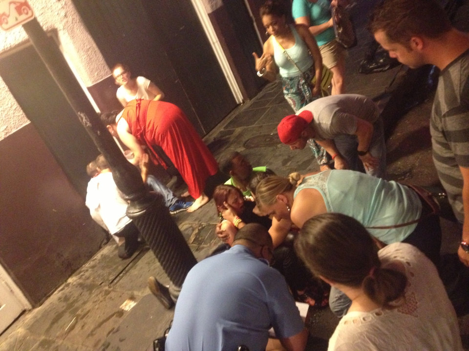 Photo - This photo released by David Minsky shows victims being assisted moments after a shooting on Bourbon Street early Sunday morning that left nine people injured, Sunday, June 29, 2014. (AP Photo/David Minsky)