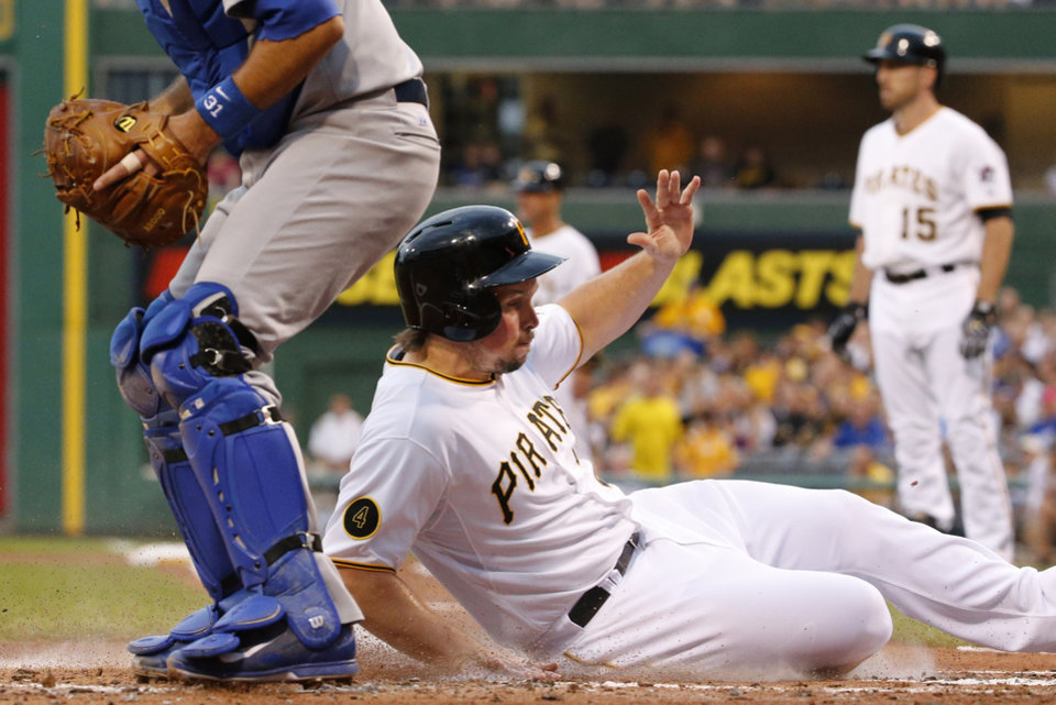 Photo - Pittsburgh Pirates' Travis Snider, front right, scores on a sacrifice fly by teammate Ike Davis (15) off Los Angeles Dodgers starting pitcher Dan Haren during the first inning of a baseball game in Pittsburgh, Wednesday, July 23, 2014. (AP Photo)