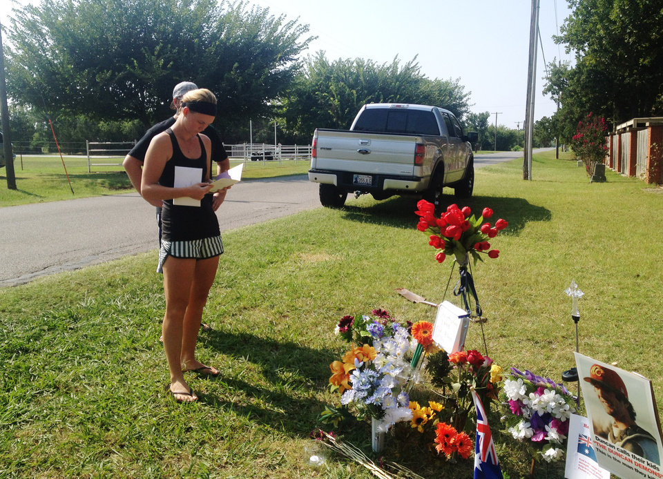 "Sarah Harper,Christopher Lane's girlfriend, stands beside a memorial along the road where police say Lane, an Australian baseball player was shot and killed Friday, Aug. 16, 2013 by three ""bored"" teenagers who decided to kill someone for fun, in Duncan, Okla. Lane, who was visiting Duncan where Harper and her family lives, had jogged past a home where the boys were staying and that apparently led to him being gunned down at random, said Police Chief Danny Ford. (AP Photo/Kristi Easton) ORG XMIT: RPKE101"