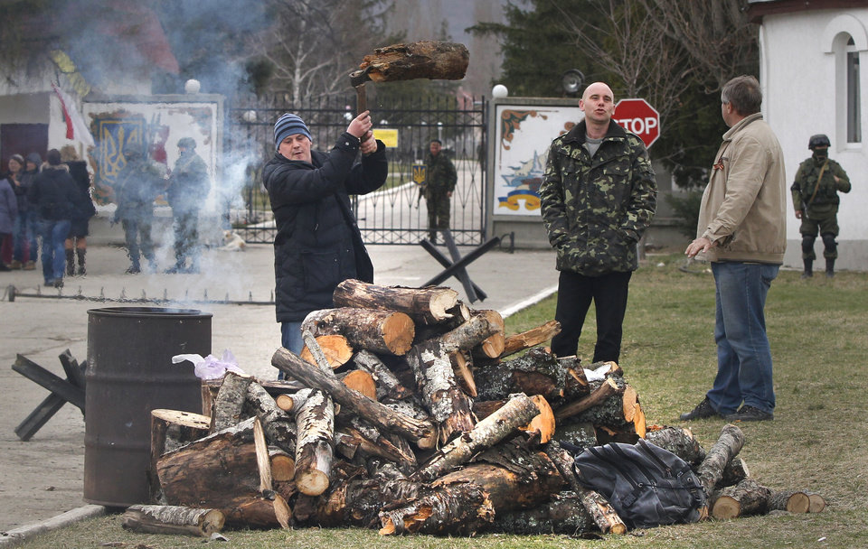 Local residents chopping wood for a bonfire as Russian soldier guards the gate of an Ukrainian infantry base in Perevalne, Ukraine, Tuesday, March 4, 2014.   Tensions remained high in the strategic Ukrainian peninsula of Crimea with troops loyal to Moscow firing warning shots to ward off protesting Ukrainian soldiers. (AP Photo/Sergei Grits)