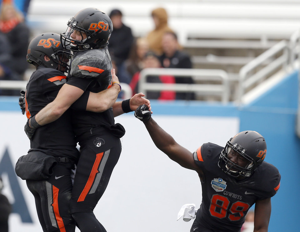 Photo - Oklahoma State's J.W. Walsh (4), Blake Webb (85) and Nick Rockwell (89) celebrate a touchdown during the Heart of Dallas Bowl football game between the Oklahoma State University (OSU) and Purdue University at the Cotton Bowl in Dallas,  Tuesday,Jan. 1, 2013. Photo by Sarah Phipps, The Oklahoman