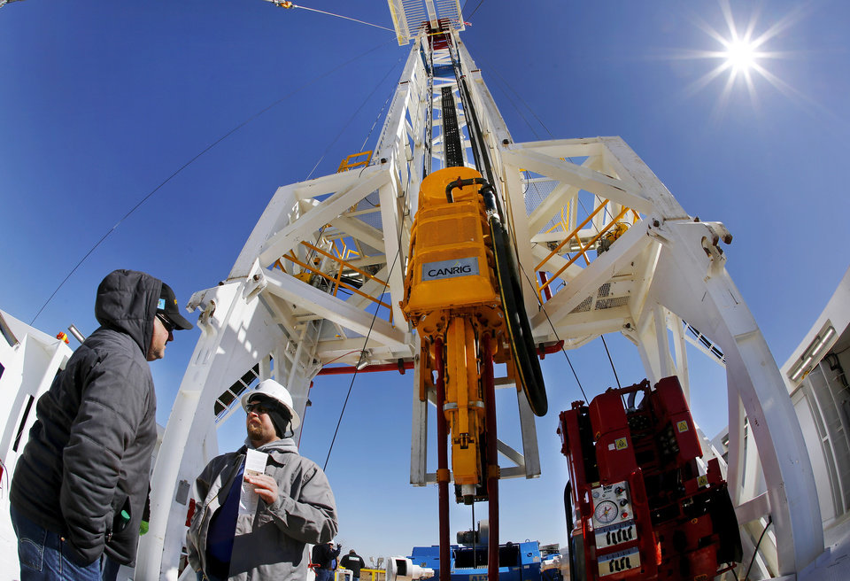 James Davis, right, a motor hand with Unit Drilling, explains features of the BOSS rig to Clay Caldwell, representing Global Energy Solutions. The men are standing on the rig floor, with the derrick towering above them. Unit Drilling Company invited hundreds of guests Wednesday, Feb. 26, 2014, to  get an up-close look its new BOSS rig at a come-and-go event at their southwest Oklahoma City manufacturing yard.       Photo by Jim Beckel, The Oklahoman