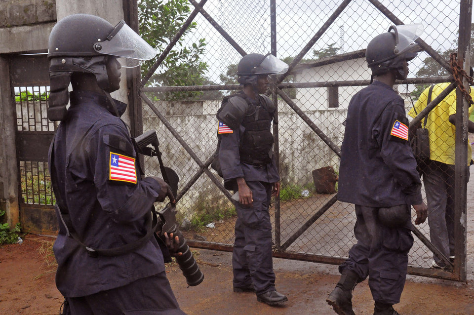 Photo - Liberian Police dressed in riot gear deploy at a MSF, 'Doctors Without Borders',  Ebola treatment center as they provide security in the city of Monrovia, Liberia, Monday, Aug. 18, 2014. Liberia's armed forces were given orders to shoot people trying to illegally cross the border from neighboring Sierra Leone, which was closed to stem the spread of Ebola, local newspaper Daily Observer reported Monday. (AP Photo/Abbas Dulleh)