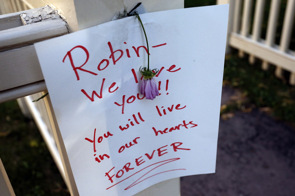 Photo - A sign and a flower are affixed to the front gate at a makeshift memorial outside the home where the 80s TV series Mork & Mindy, starring the late Robin Williams, was set, in Boulder, Colo., Tuesday Aug. 12, 2014. Williams, the Academy Award winner and comic supernova whose explosions of pop culture riffs and impressions dazzled audiences for decades and made him a gleamy-eyed laureate for the Information Age, died Monday, Aug. 11 in an apparent suicide. He was 63. (AP Photo/Brennan Linsley)
