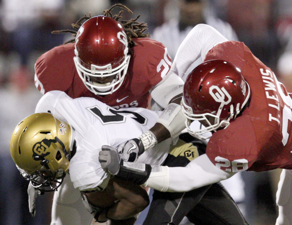 Photo - OU's Quinton Carter, top, and Travis Lewis bring down Colorado's Rodney Stewart during the college football game between the University of Oklahoma (OU) Sooners and the University of Colorado Buffaloes at Gaylord Family-Oklahoma Memorial Stadium in Norman, Okla., Saturday, October 30, 2010. Photo by Bryan Terry, The Oklahoman