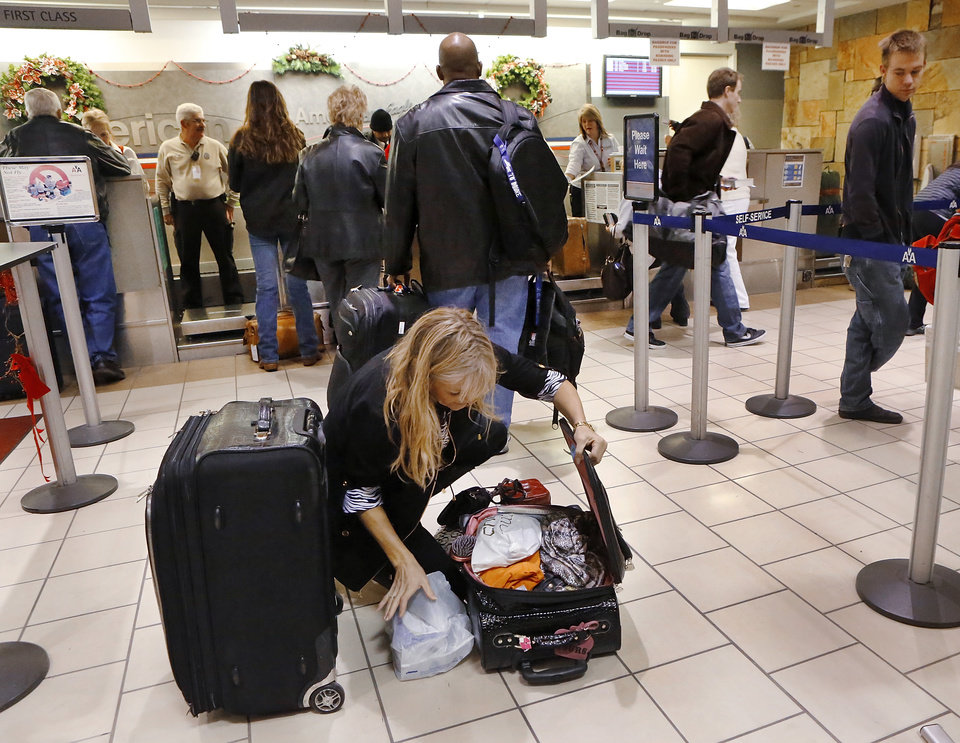 Dana Tenaglia adds last minute shopping items to her luggage as she rearrange the contents of her suitcase to make everything fit while waiting in line at an American Airlines ticket counter at Will Rogers World Airport Thursday morning, Dec. 20, 2012. Tenaglia is returning to her home in Florida after celebrating an early Christmas with family and friends in Enid. Photo by Jim Beckel, The Oklahoman