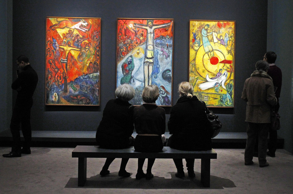 Photo - Members of the media view a triptych by Russian artist Marc Chagall before the opening of the exhibition: Chagall, between War and Peace, at the Luxembourg museum in Paris, Tuesday Feb. 19, 2013. The exhibition starts February 21 and ends July 21, 2013.  Paintings are from left: 1937, Resistance, 1948, Resurrection, 1952, Liberation.(AP Photo/Remy de la Mauviniere)