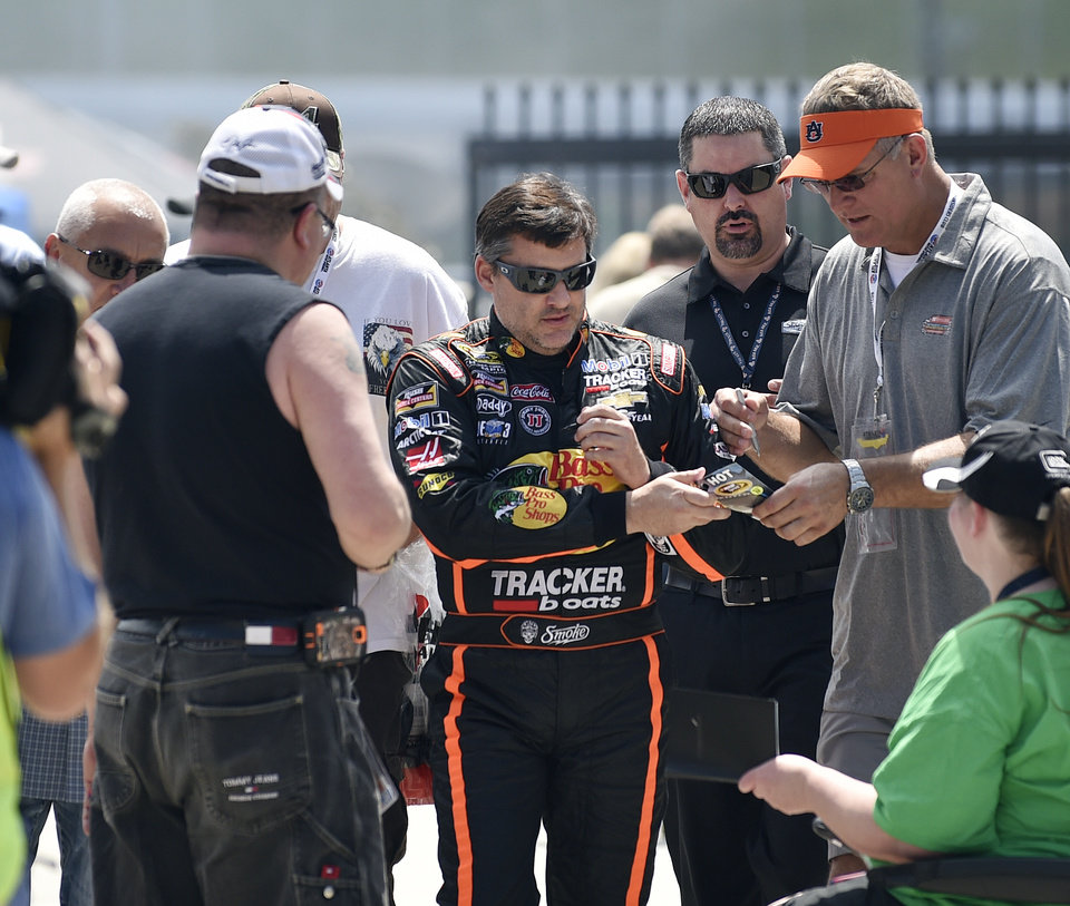 Photo - NASCAR driver Tony Stewart signs autographs as he makes his way to his car to practice for Sunday's auto race at Atlanta Motor Speedway in Hampton, Ga., Friday, Aug. 29, 2014. Sunday's race will be his first since his car struck and killed a fellow driver during a sprint race in New York three weeks ago. (AP Photo/John Bazemore)