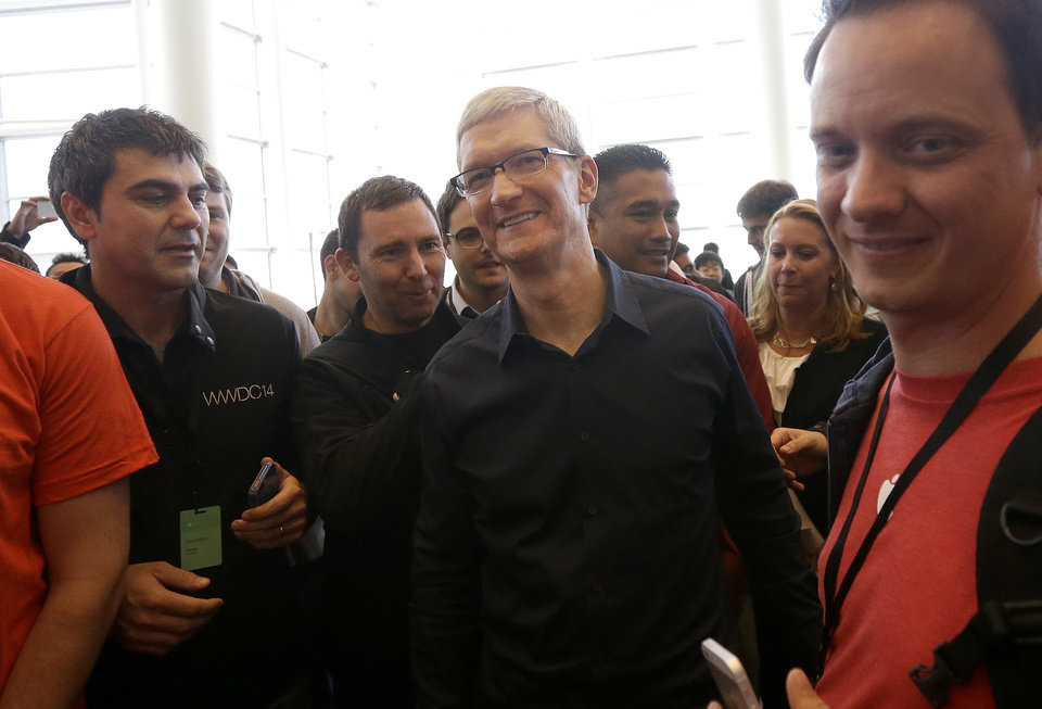 Photo - Apple CEO Tim Cook smiles after getting a demonstration of CarPlay in a Ford Mustang at the Apple Worldwide Developers Conference in San Francisco, Monday, June 2, 2014. (AP Photo/Jeff Chiu)