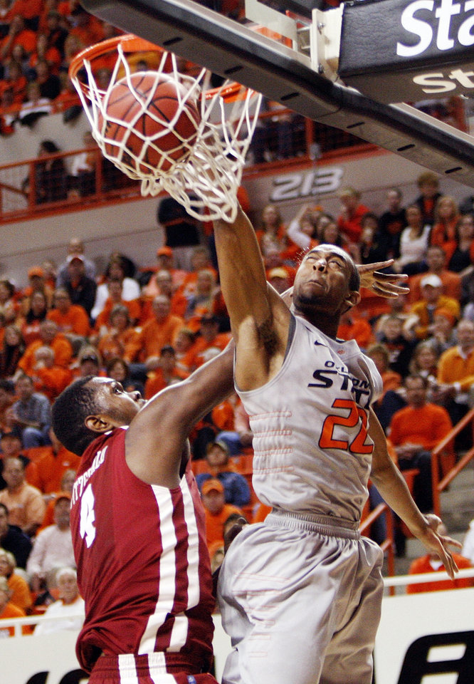 Photo - OSU's Markel Brown (22) dunks the ball over Andrew Fitzgerald (4) of OU in the second half during the Bedlam men's college basketball game between the Oklahoma State University Cowboys and the University of Oklahoma Sooners at Gallagher-Iba Arena in Stillwater, Okla., Monday, Jan. 9, 2012. OSU beat OU, 72-65. Photo by Nate Billings, The Oklahoman
