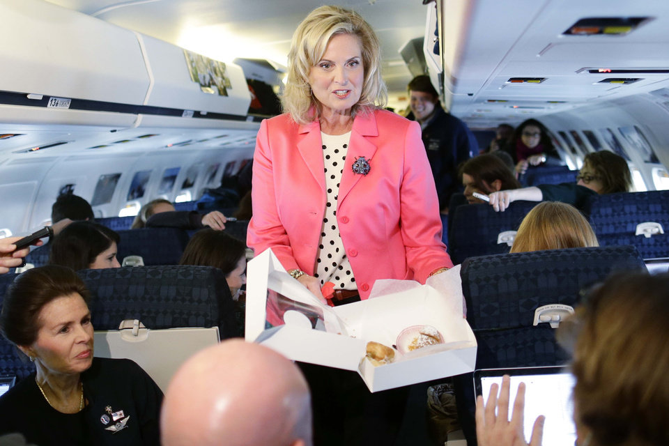 Photo -   Ann Romney, wife of Republican presidential candidate and former Massachusetts Gov. Mitt Romney, hands out pastry to reporters on the plane after a campaign event at Portsmouth International Airport, in Newington, N.H., Saturday, Nov. 3, 2012. (AP Photo/Charles Dharapak)
