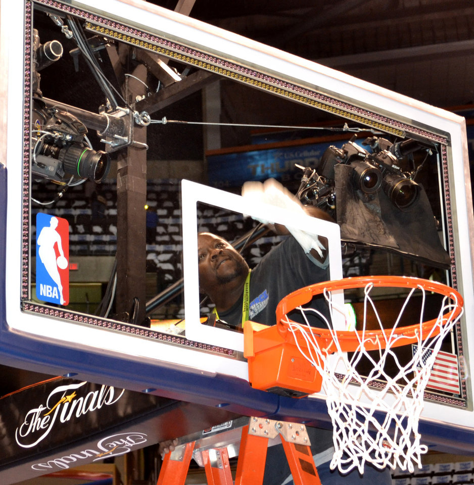 Photo - Ronnie White cleans the backboard at the Chesapeake Energy Arena for game two of the NBA Finals between the Oklahoma City Thunder and the Miami Heat Thursday June 14, 2012. Photo by Zeke Campfield, The Oklahoman