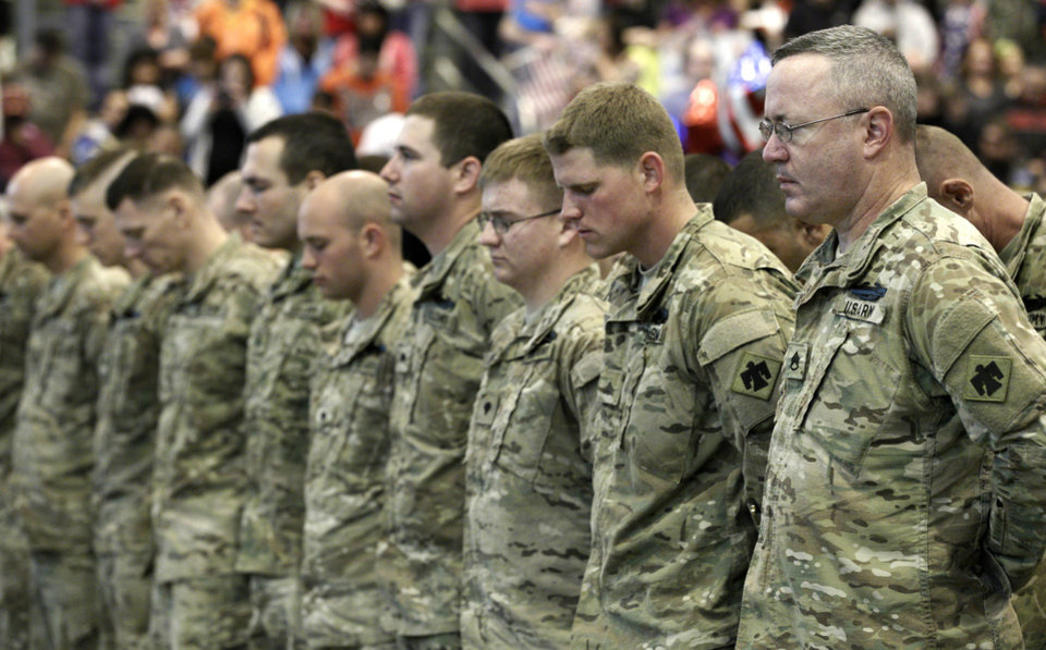 Returning members of the 45th Infantry Brigade of the Oklahoma National Guard bow their heads in memory of the 14 Oklahoma Guard soldiers killed during their recent deployment, at a welcome home ceremony for 130 of the group in Oklahoma City, Saturday, March 3, 2012. (AP Photo/Sue Ogrocki) ORG XMIT: OKSO104