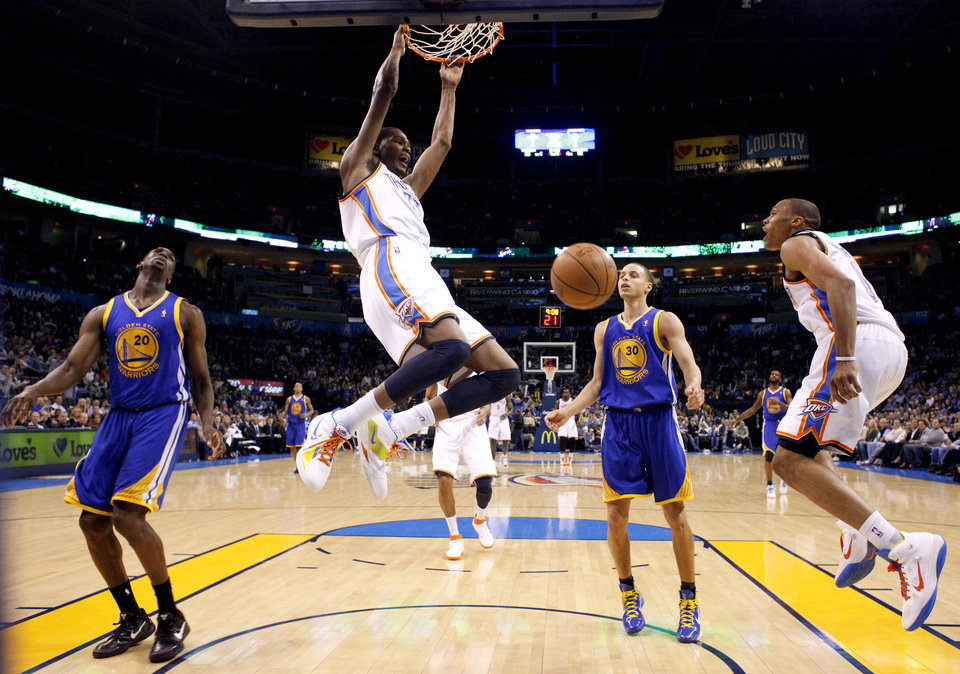 Oklahoma City\'s Kevin Durant (35) dunks the ball between Golden State\'s Ekpe Udoh (20) and Stephen Curry (30) as Oklahoma City\'s Russell Westbrook (0) reacts during the NBA basketball game between the Oklahoma City Thunder and the Golden State Warriors at the Oklahoma City Arena, Tuesday, March 29, 2011. Photo by Bryan Terry, The Oklahoman
