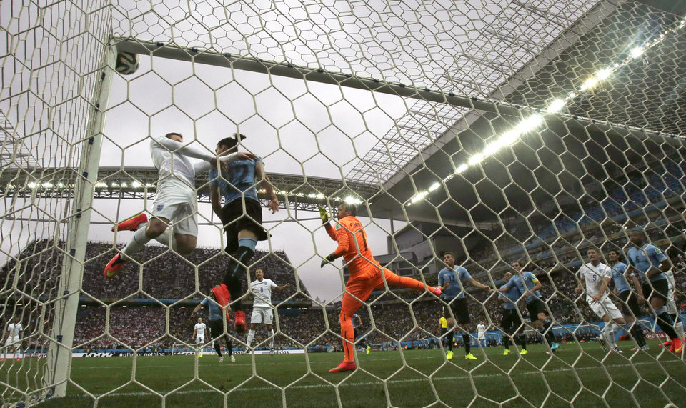 Photo - England's Wayne Rooney, left, in white, heads the ball at the crossbar as Uruguay's goalkeeper Fernando Muslera, right in orange, watches during the group D World Cup soccer match between Uruguay and England at the Itaquerao Stadium in Sao Paulo, Brazil, Thursday, June 19, 2014.  (AP Photo/Thanassis Stavrakis)