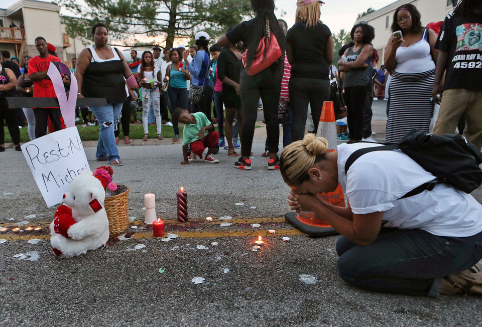 Photo - Meghan O'Donnell, 29, from St. Louis, prays at the spot where Michael Brown was killed, Sunday evening, Aug. 10, 2014, in Ferguson, Mo. A few thousand people have crammed the street where a black man was shot multiple times by a suburban St. Louis police officer. The candlelight vigil Sunday night was for 18-year-old Michael Brown, who died a day earlier. Police say he was unarmed. (AP Photo/St. Louis Post-Dispatch, J.B. Forbes)