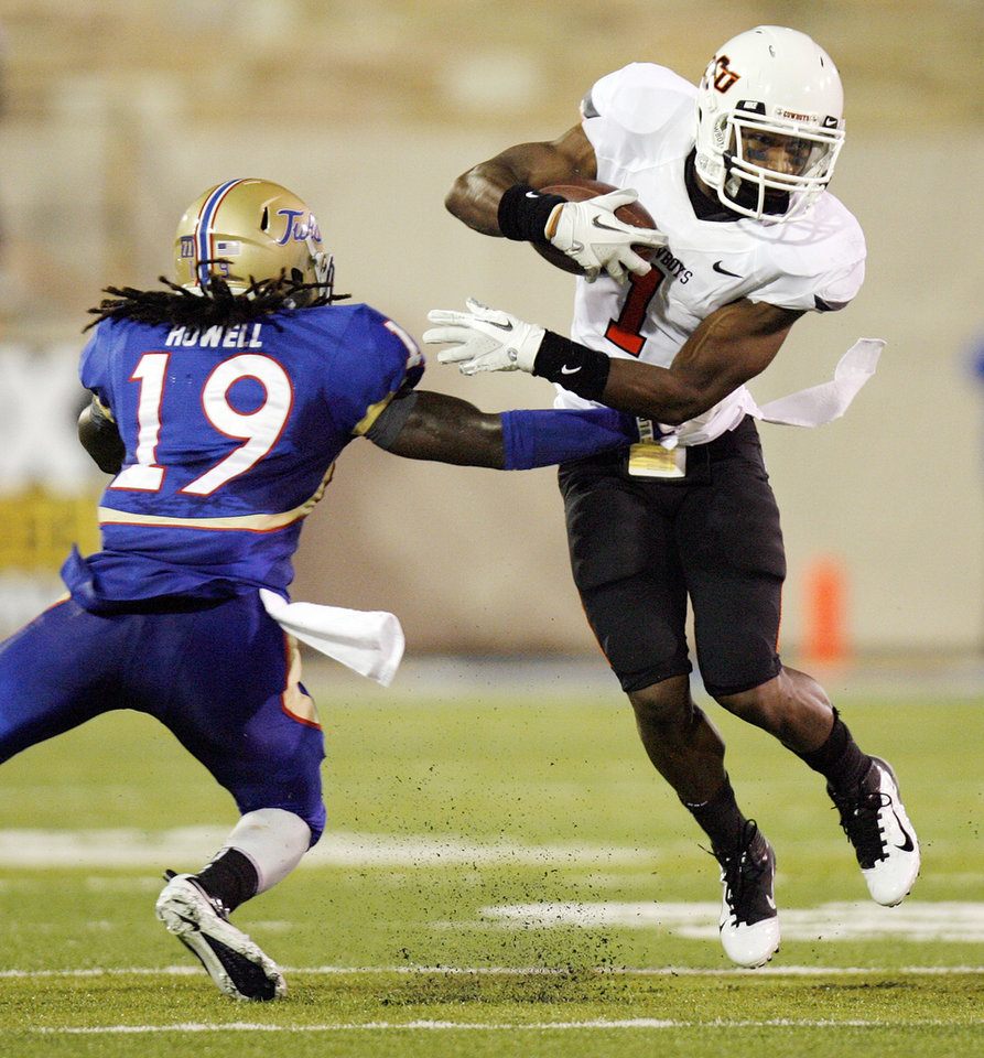 Photo - OSU's Joseph Randle (1) tries to avoid a tackle by Milton Howell (19) of TU in the first quarter during a college football game between the Oklahoma State University Cowboys and the University of Tulsa Golden Hurricane at H.A. Chapman Stadium in Tulsa, Okla., Sunday morning, Sept. 18, 2011. Photo by Nate Billings, The Oklahoman
