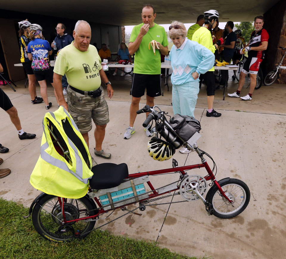 Photo - Frank Lotito, of Noble, shows off his electric and pedal power bike to other riders at a Bike to Work rally Friday at Andrews Park in Norman. PHOTO BY STEVE SISNEY, THE OKLAHOMAN  STEVE SISNEY