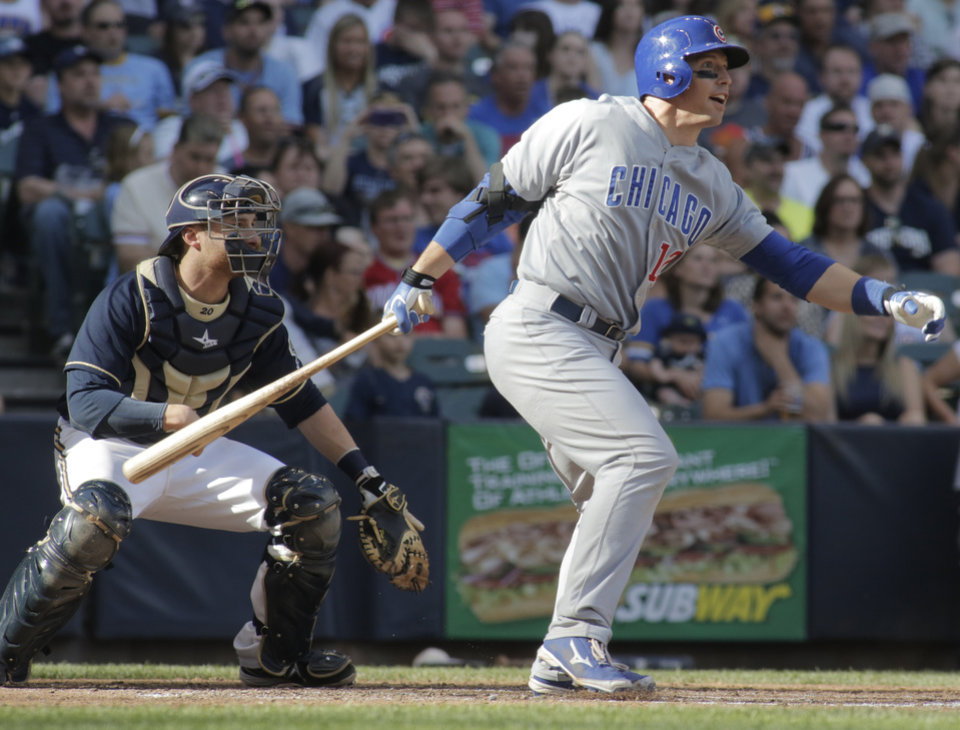 Photo - Chicago Cubs catcher John Baker hits an RBI single against the Milwaukee Brewers during the sixth inning of a baseball game Saturday, May 31, 2014, in Milwaukee. (AP Photo/Darren Hauck)