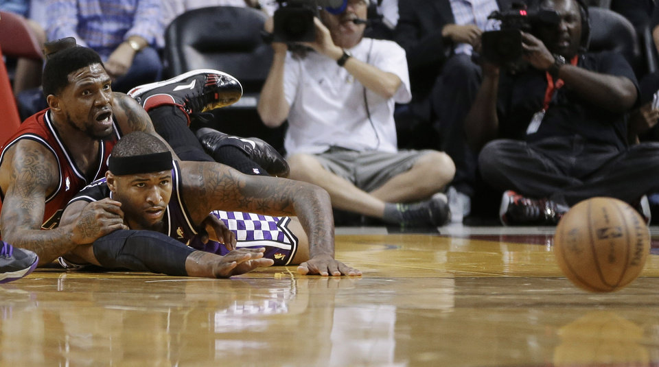 Miami Heat's Udonis Haslem, top, and Sacramento Kings' DeMarcus Cousins watch a loose ball during the first half of an NBA basketball game in Miami, Tuesday, Feb. 26, 2013. (AP Photo/J Pat Carter)