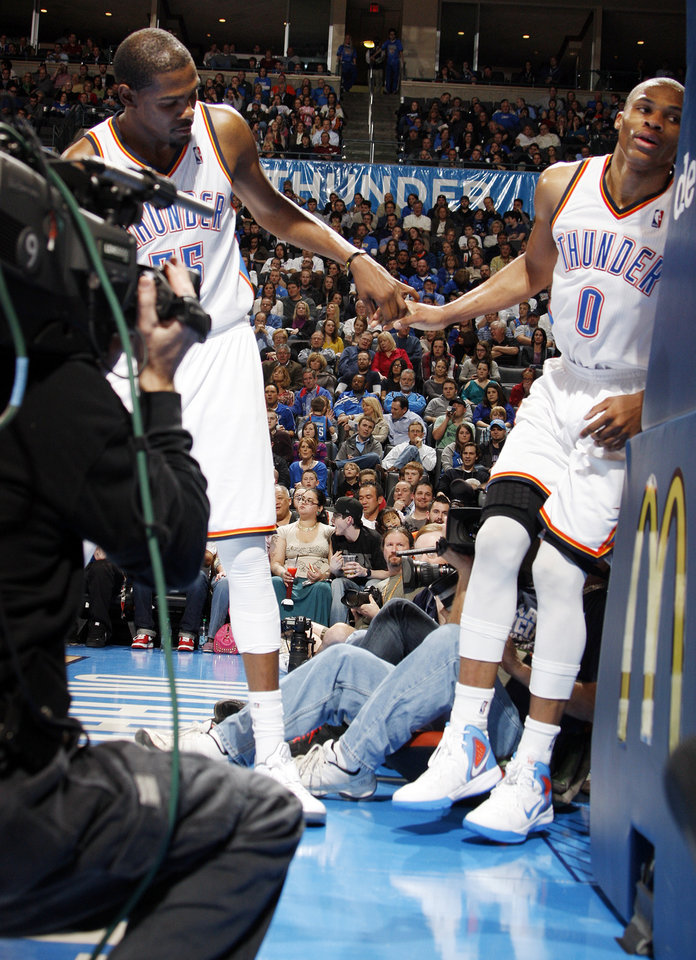 Oklahoma City's Kevin Durant (35), left, helps Russell Westbrook (0) back on the court after Westbrook was hurt on a play in the third quarter during the NBA basketball game between the Oklahoma City Thunder and the Golden State Warriors at the Chesapeake Energy Arena in Oklahoma City, Friday, Feb. 17, 2012. The Thunder won, 110-87. Photo by Nate Billings, The Oklahoman