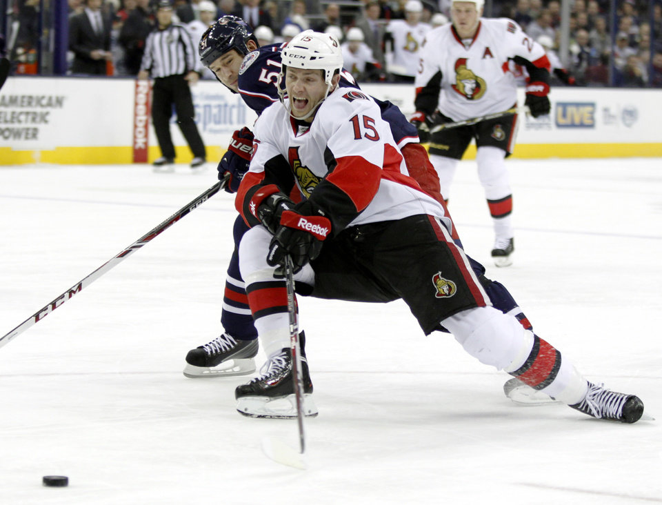 Photo - Ottawa Senators' Zack Smith, right, reaches for the puck against Columbus Blue Jackets' Fedor Tyutin of Russia in the first period of an NHL hockey game in Columbus, Ohio, Tuesday, Nov.5, 2013. (AP Photo/Paul Vernon)