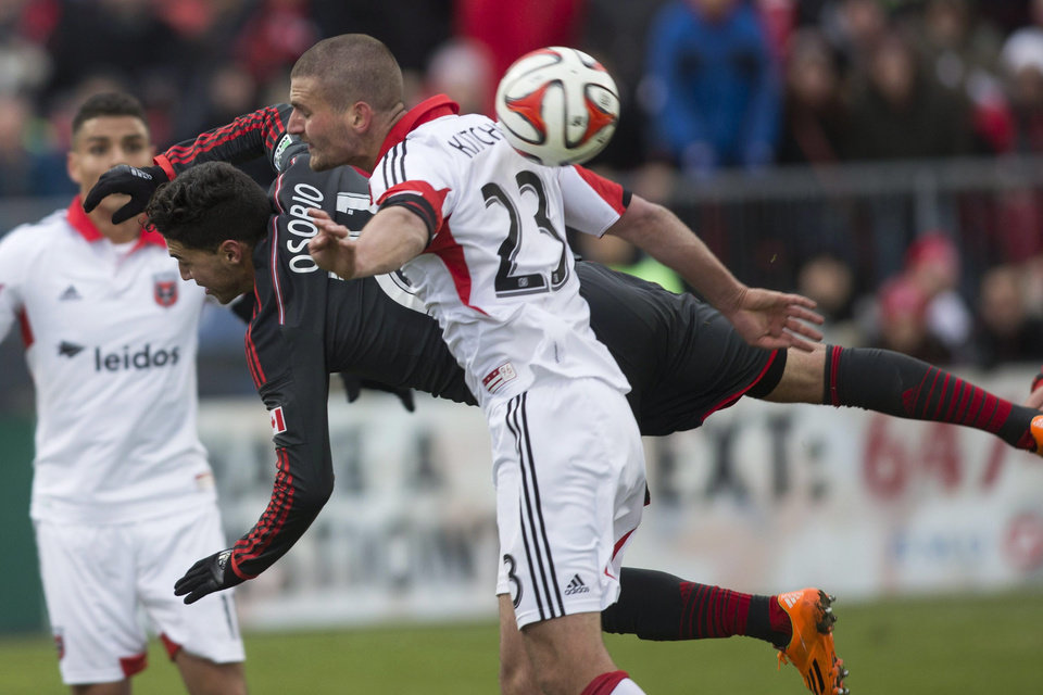 Photo - Toronto FC 's Jonathan Osorio, center, tries to connect with a cross as D.C. United's Perry Kitchen covers during the second half of an MLS soccer game in Toronto on Saturday, March 22, 2014. (AP Photo/The Canadian Press, Chris Young)