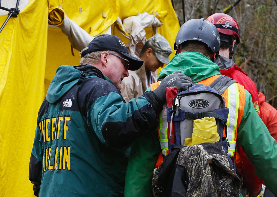Photo - A sheriff chaplain offers a few words to a rescue worker as he enters the decontamination tent area at the west side of the mudslide on Highway 530 near mile marker 37  in Arlington, Wash., on Sunday, March 30, 2014. Periods of rain and wind have hampered efforts the past two days, with some rain showers continuing today. Last night, the confirmed fatalities list was updated to 18, with the number of those missing falling from 90 to 30. (AP Photo/Rick Wilking, Pool)