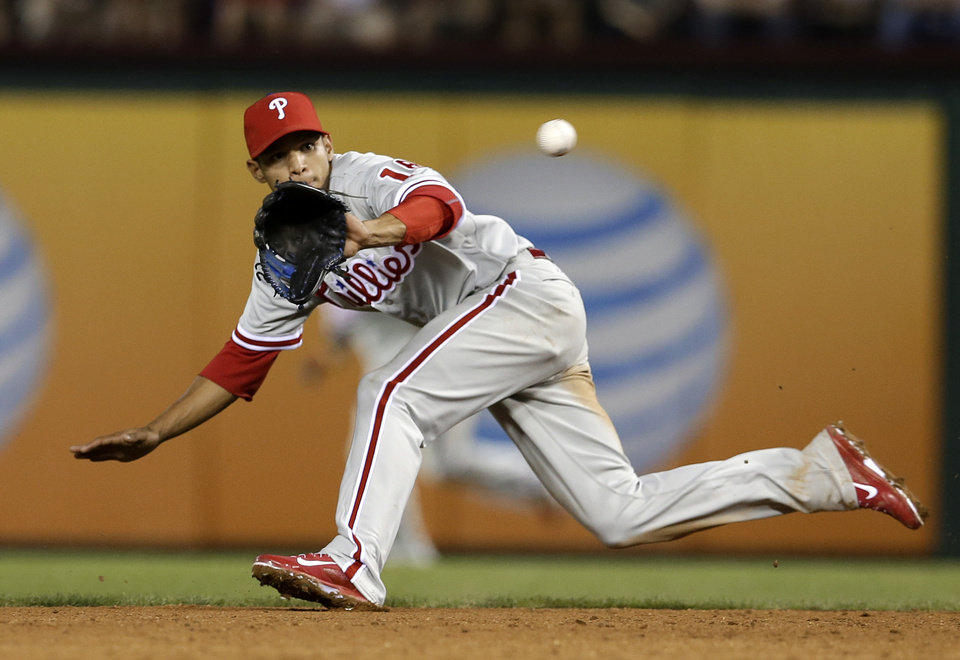 Photo - Philadelphia Phillies second baseman Cesar Hernandez chases down grounder by Texas Rangers' Alex Rios, who was out at first in the third inning of a baseball game, Tuesday, April 1, 2014, in Arlington, Texas. (AP Photo/Tony Gutierrez)