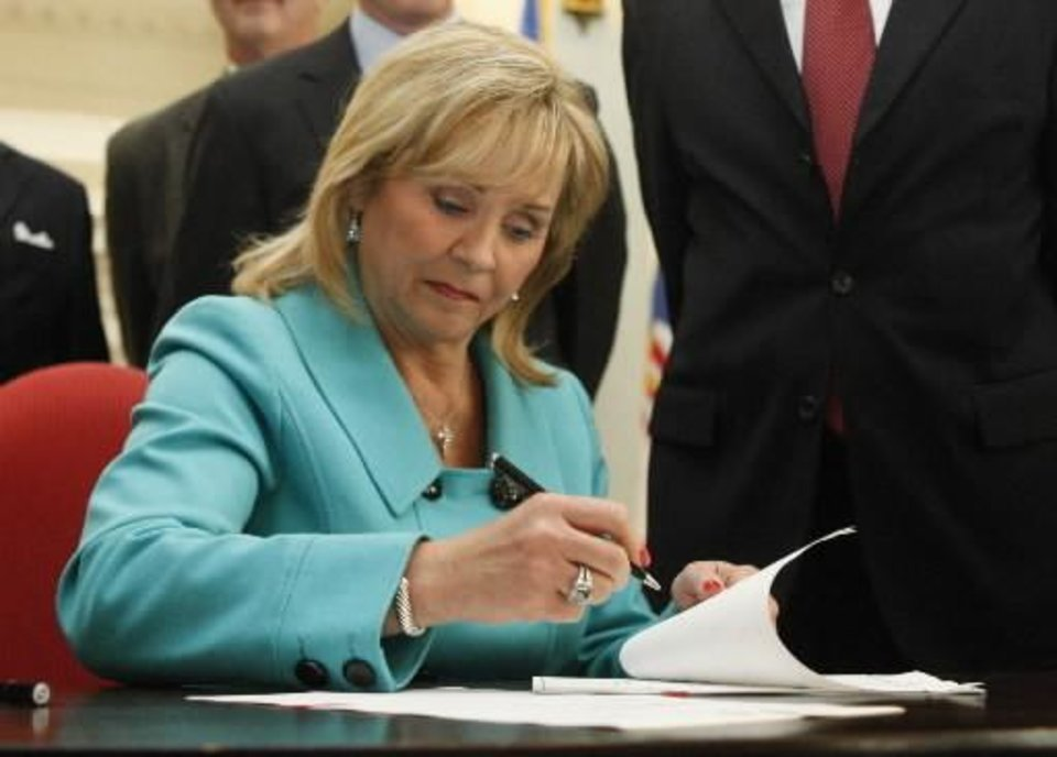 Oklahoma Gov. Mary Fallin signs one of five separate bills designed to shore up the state's underfunded pension systems by requiring new public employees and teachers to work longer and mandating that cost-of-living adjustments be funded by the Legislature, in Oklahoma City, Tuesday, May 10, 2011. (AP Photo/Sue Ogrocki)