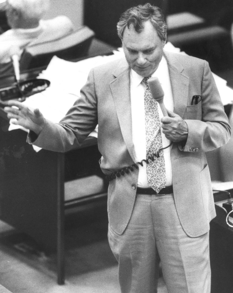 Photo - Gene Stipe,  long-time State Senator from McAlester, gestures to make a point during discussion of a bill in the State Senate Chamber at the state capitol.  Staff photo by Doug Hoke taken 6/30/87.