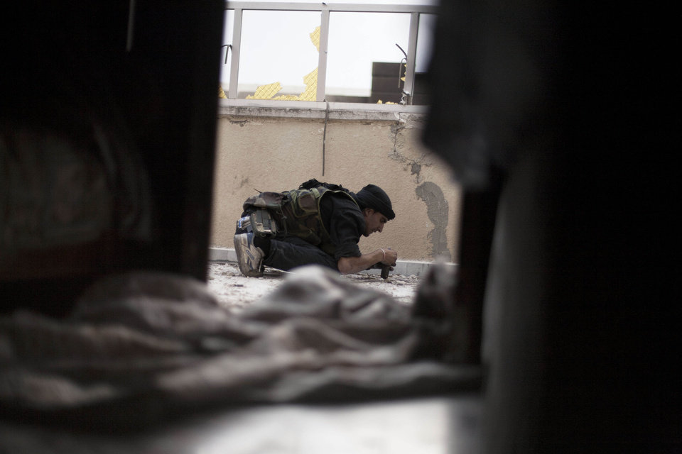Photo -   A Free Syrian Army soldier checks a home-made explosive while taking cover during a fight against Syrian Army troops in Saif Al Dawle district in Aleppo, Syria, Tuesday, Oct. 2, 2012. (AP Photo/ Manu Brabo)