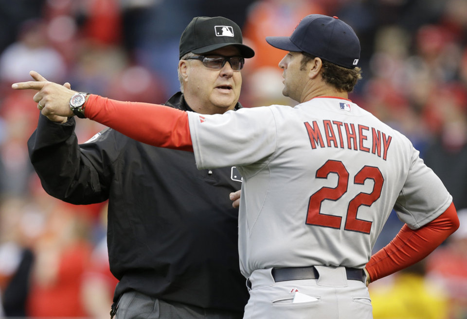 Photo - Crew chief Gary Cederstrom, left, explains a ruling to St. Louis Cardinals manager Mike Matheny in the seventh inning of a baseball game against the Cincinnati Reds, Thursday, April 3, 2014, in Cincinnati. St. Louis won 7-6. (AP Photo/Al Behrman)