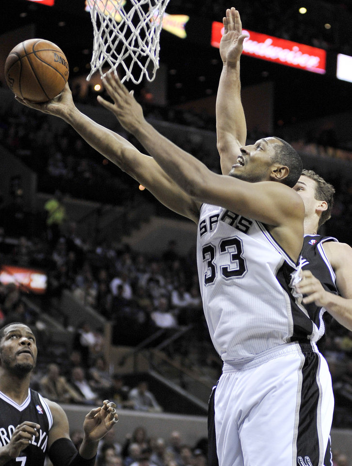 Photo - San Antonio Spurs' Boris Diaw shoots ahead of Brooklyn Nets' Kris Humphries, right, during the first half of an NBA basketball game, Monday, Dec. 31, 2012, in San Antonio. (AP Photo/Darren Abate)