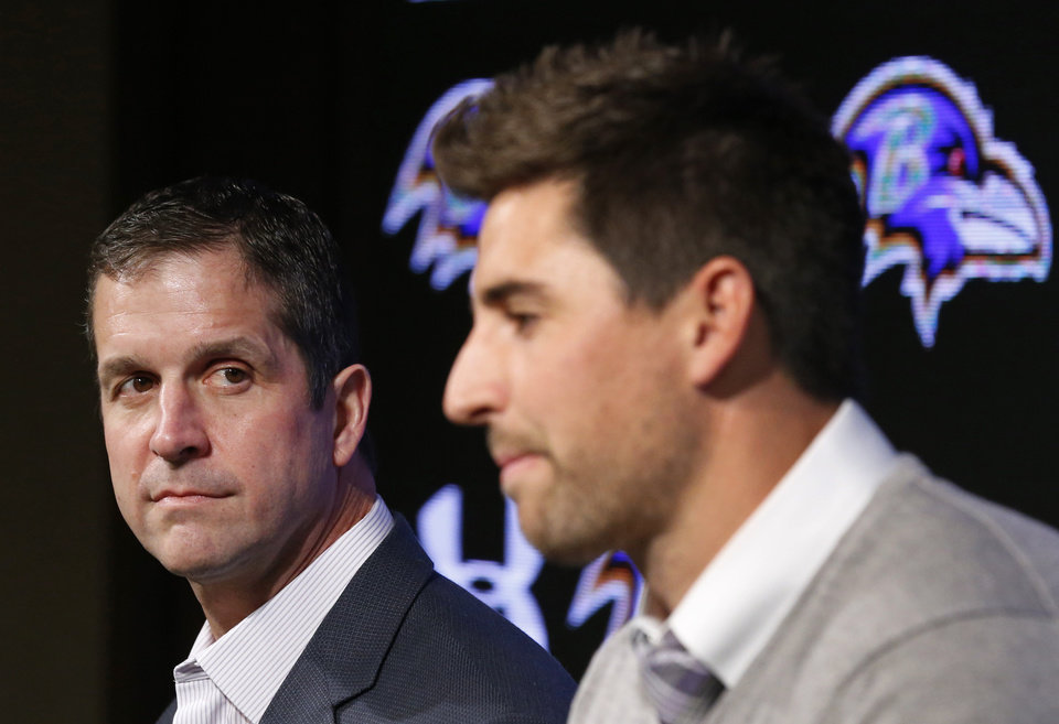 Photo - Baltimore Ravens head coach John Harbaugh, left, listens as tight end Dennis Pitta discusses his new five-year contract during an NFL football news conference, Wednesday, March 5, 2014, at the Ravens practice facility in Owings Mills, Md.  (AP Photo/Patrick Semansky)