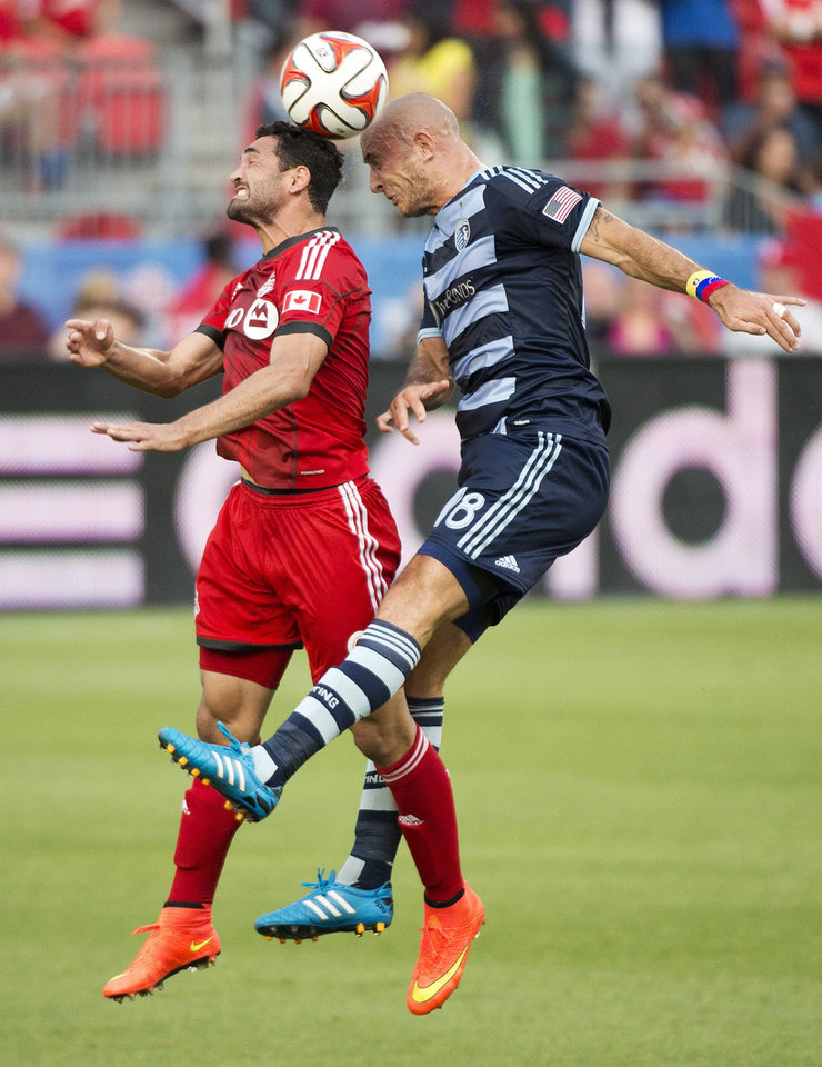 Photo - Toronto FC forward Gilberto, left, heads the ball with Sporting Kansas City midfielder Victor Munoz during the first half of an MLS soccer game Saturday, July 26, 2014, in Toronto. (AP Photo/The Canadian Press, Nathan Denette)
