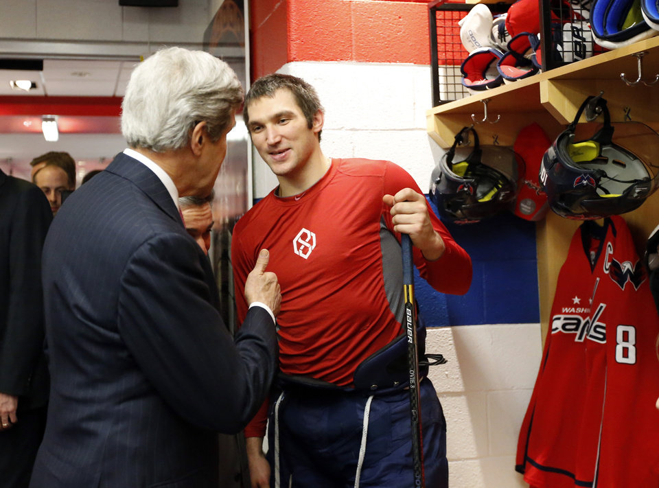Photo - ** CORRECTS DATE to FEB. 6 ** Secretary of State John Kerry, left, gives thumbs up to Washington Capitals right wing Alex Ovechkin, from Russia, in the locker room before their game with the Winnipeg Jets, Thursday, Feb. 6, 2014, in Washington. Kerry was greeting players that have been selected for their country's Olympic hockey team. (AP Photo/Alex Brandon, Pool)