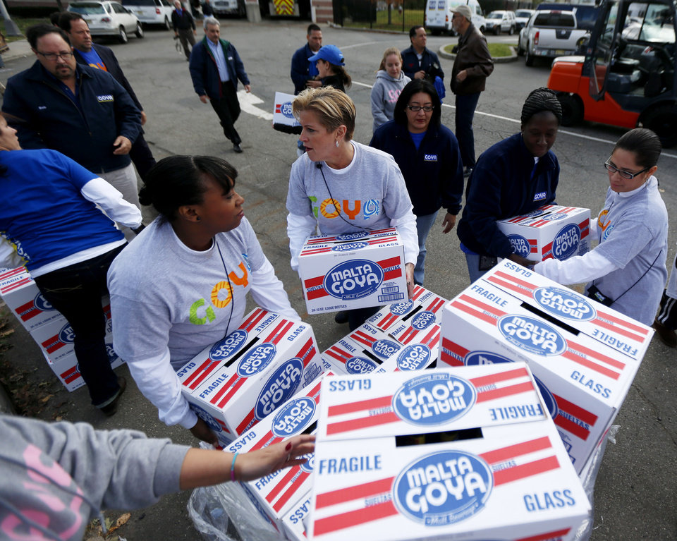 Volunteers load food products donated by Goya at the Jersey City Office of Emergency Management, Friday, Nov. 2, 2012, in Jersey City, N.J. The products will go to six different locations around Jersey City to feed those displaced by Superstorm Sandy. (AP Photo/Julio Cortez)